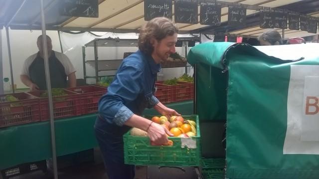 Chargement des fruits et légumes dans le triporteur.